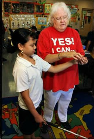 Becki Forsell teaching an elementary boy on using the white cane