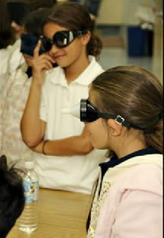 Elementary girls wearing special glasses to experience being blind